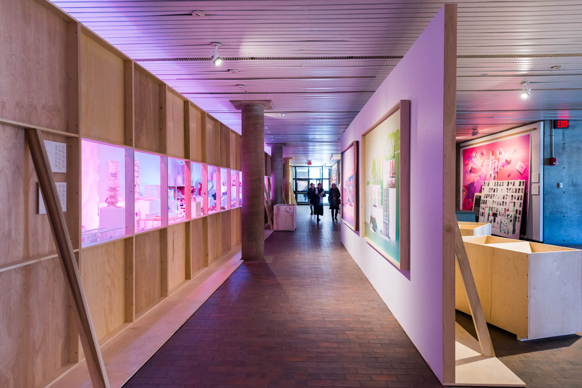 A view down a constructed hallway. One wall is a plain plywood windowed wall showcasing select student models cross-it in blue and pink hues, and the other has two hanging photos.