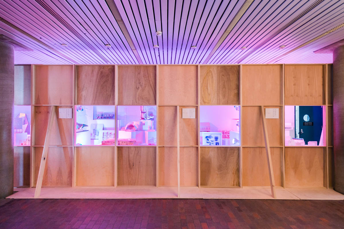 A plain plywood wall obstructing student models brightly cross lit in blue and pink hues. Square windows showcase selected views.