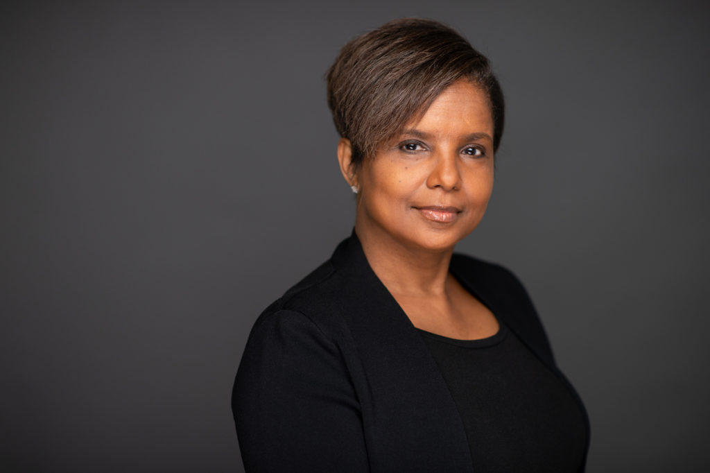 Headshot of Sheila Foster, a black woman who has short brown hair and wears black. The background is gray.