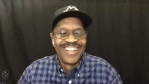 Black man wearing a black hat and a purple plaid shirt sits in front of a black curtain