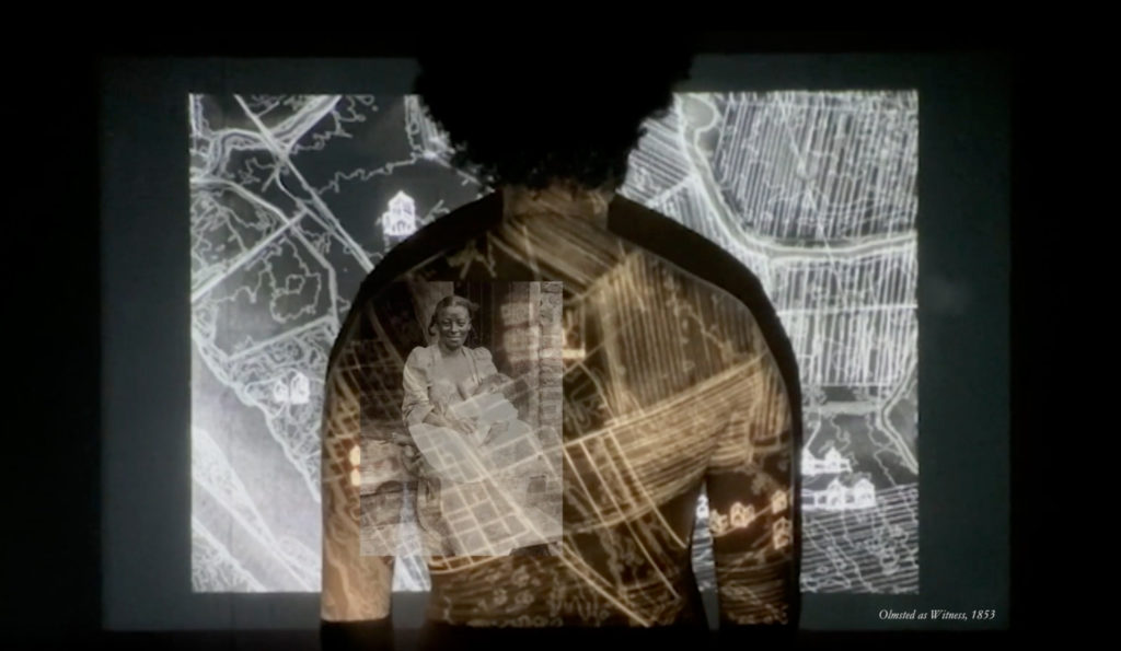 Still of video showing visual projections showing historic plantation life onto man's back