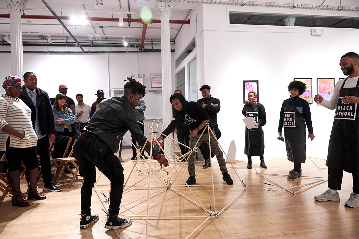 A group of people standing in a circle in a gallery space, with two people at the center working with a geometric structure made of wooden dowels.