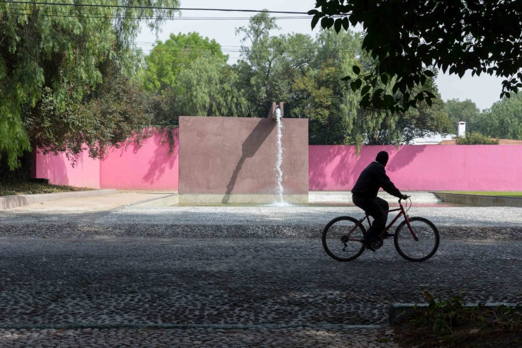 Image of man riding bike (silhouette) in front of pink Barragan wall