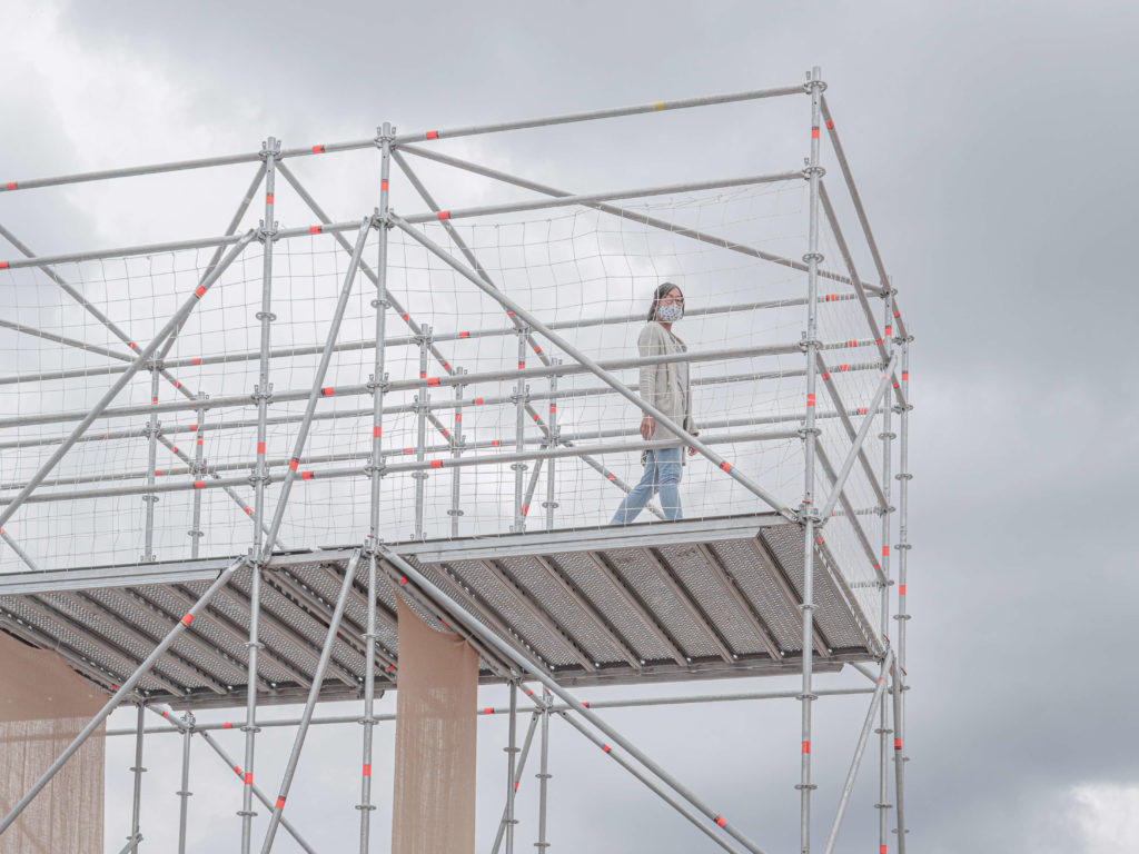 Masked woman walking on elevated scaffolding.