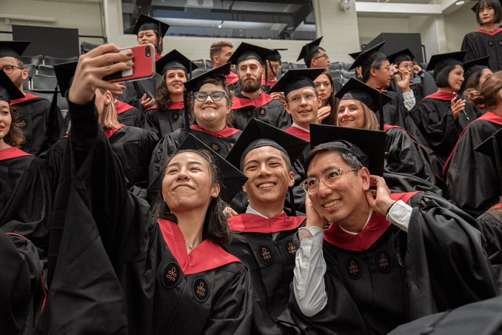 Graduates wearing commencement robes pose for a selfie.