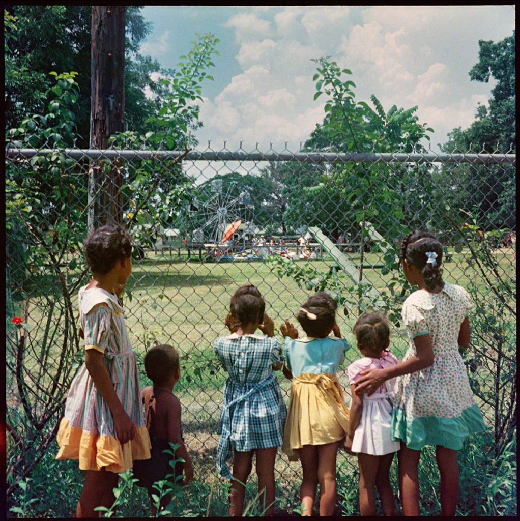 Photograph of six young children peering through a chainlink fence into a park.