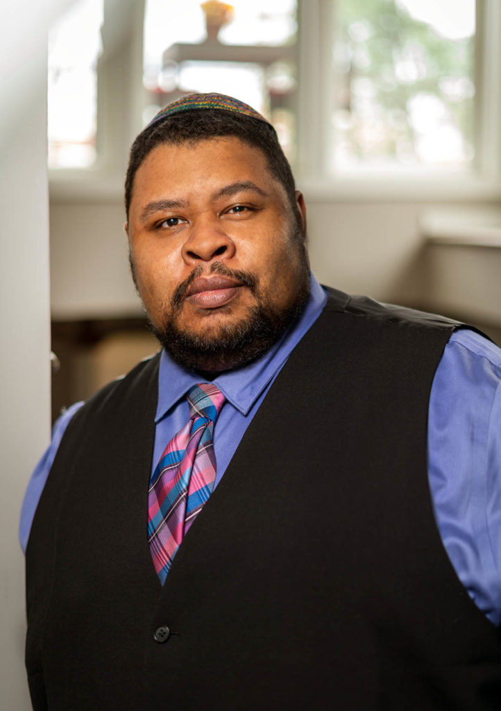 Headshot of Michael Twitty, who wears a black vest over a blue shirt with a pink and blue tie.