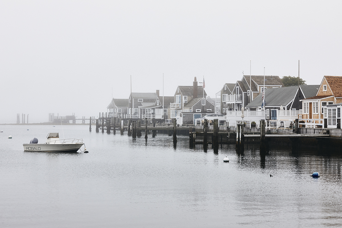 Houses and a boat on the water with morning fog