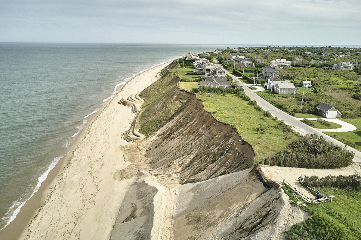 Eroded coastal shore with houses above small cliff