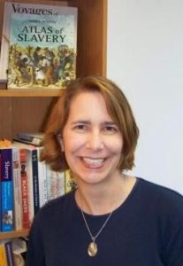 A white woman with short blond hair wearing a navy crewneck sweater and smiling, stands in front of a bookshelf